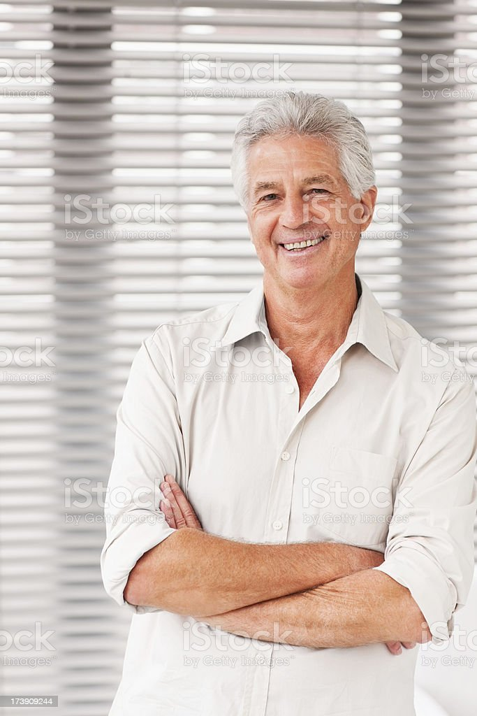 Smiling senior man standing with arms crossed royalty-free stock photo
