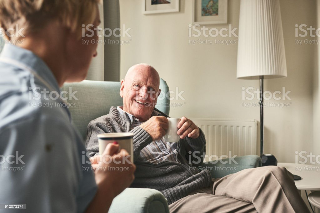 Smiling senior man talking to female caregiver stock photo