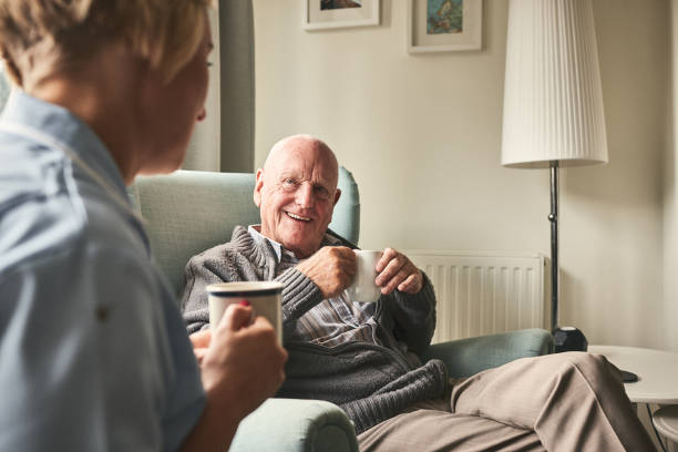 Smiling senior man talking to female caregiver Smiling senior man with cup of coffee talking to female caregiver sitting in front at care home aging stock pictures, royalty-free photos & images