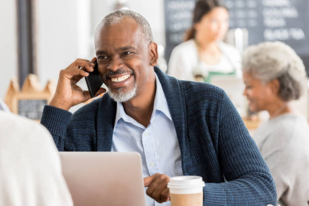 Smiling senior man talks on smart phone in cafe stock photo