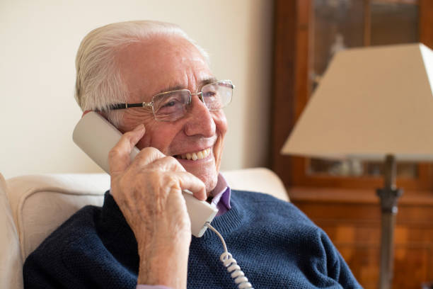 Smiling Senior Man Using Phone At Home Smiling Senior Man Using Phone At Home only senior men stock pictures, royalty-free photos & images