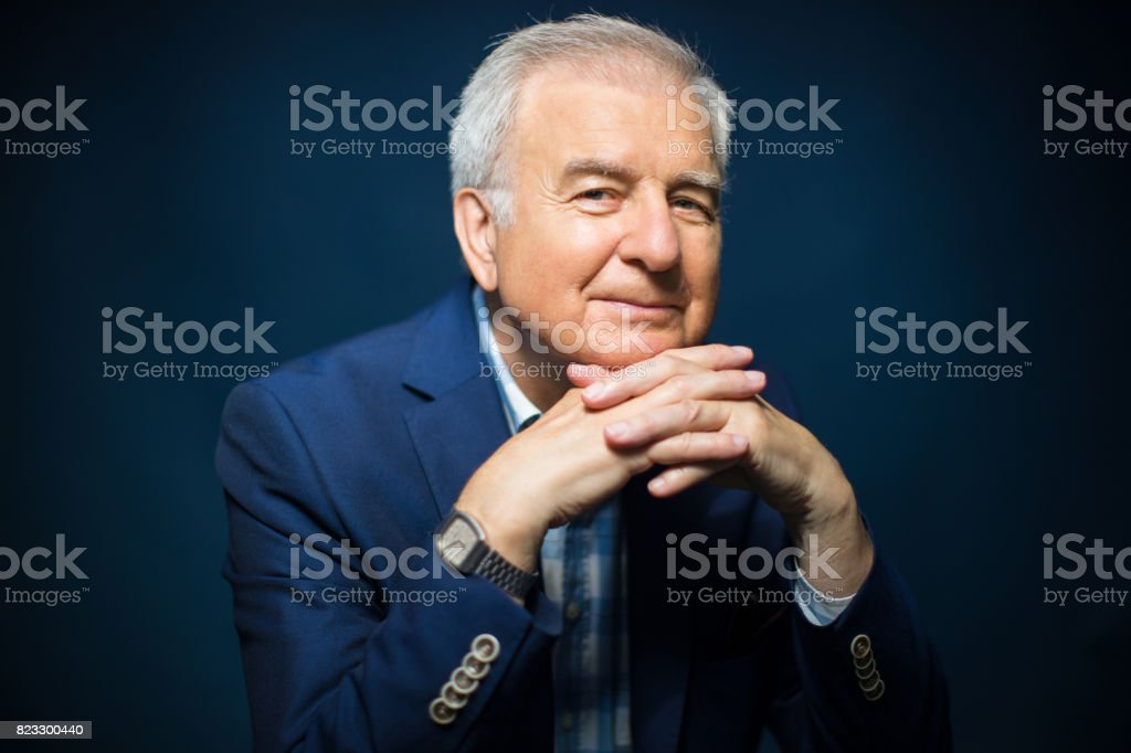 Smiling Senior Man With Hands Clasped stock photo