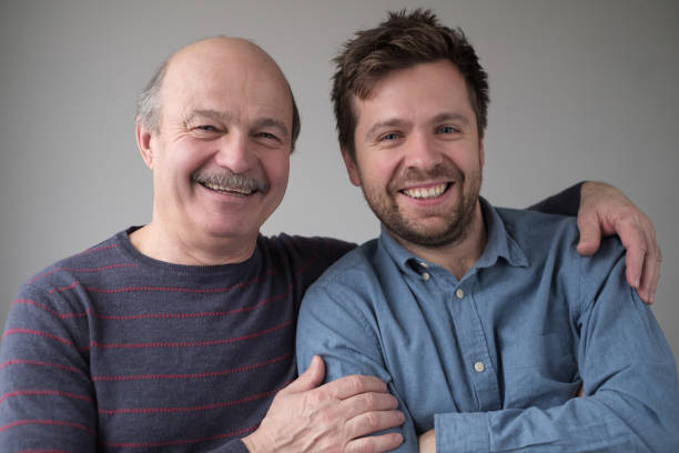 Smiling senior man with his grown up son smiling having positive mood stock photo
