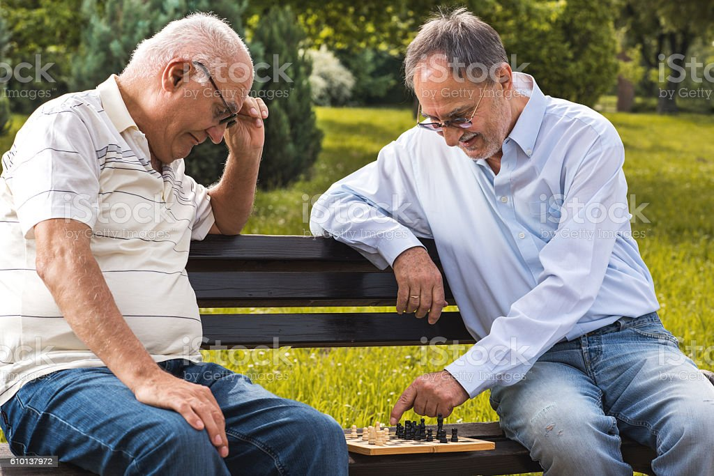 Smiling senior men playing chess in the park. stock photo
