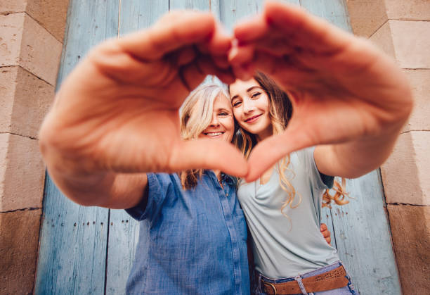 Lächelnde senior Mutter und Tochter machen eine Herzform mit ihren Händen – Foto
