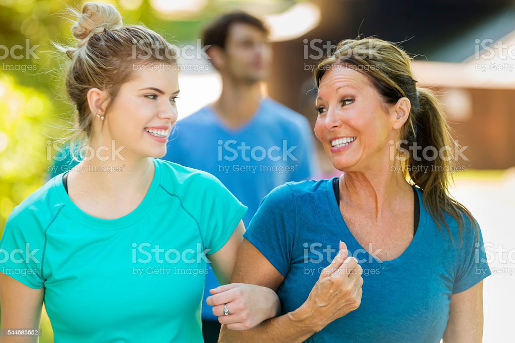 Smiling senior mother and her daughter walking together stock photo