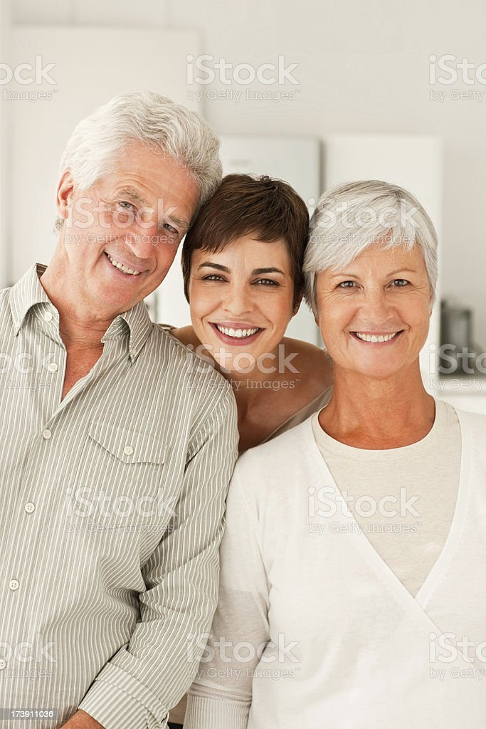 Smiling senior parents with their daughter stock photo