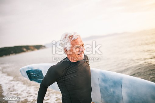 Portrait of a senior surfer holding his surfboard, being satisfied after a good surfing day