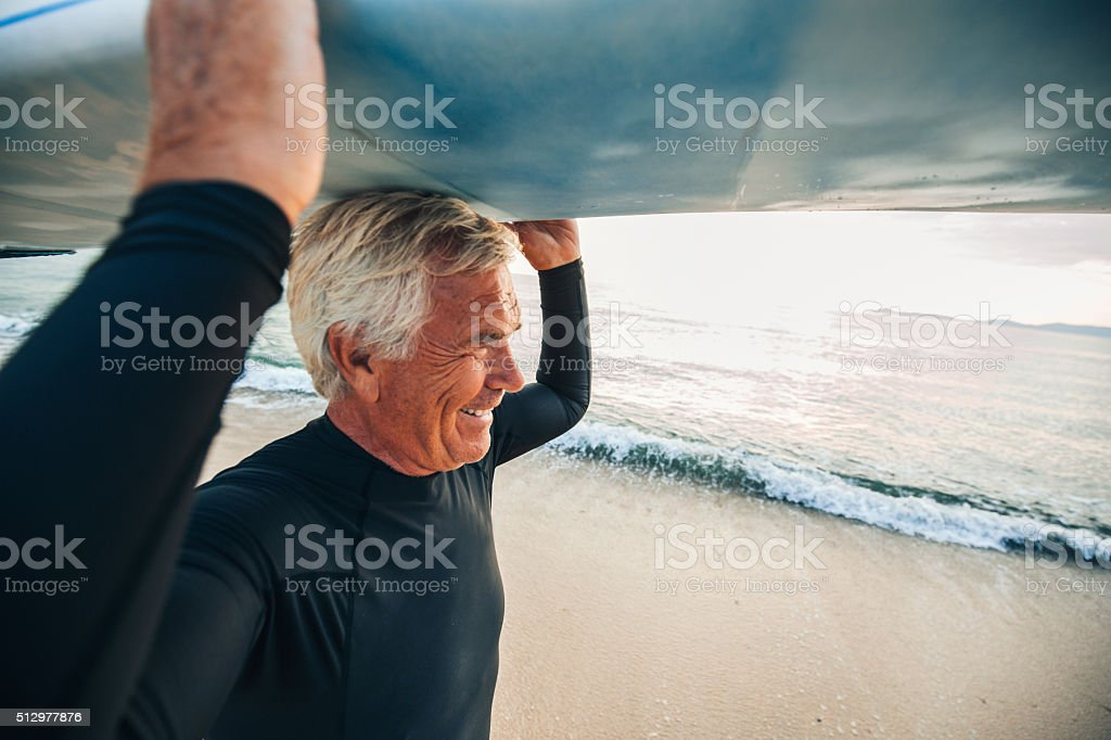 Portrait of a smiling senior surfer coming out of the water after a...