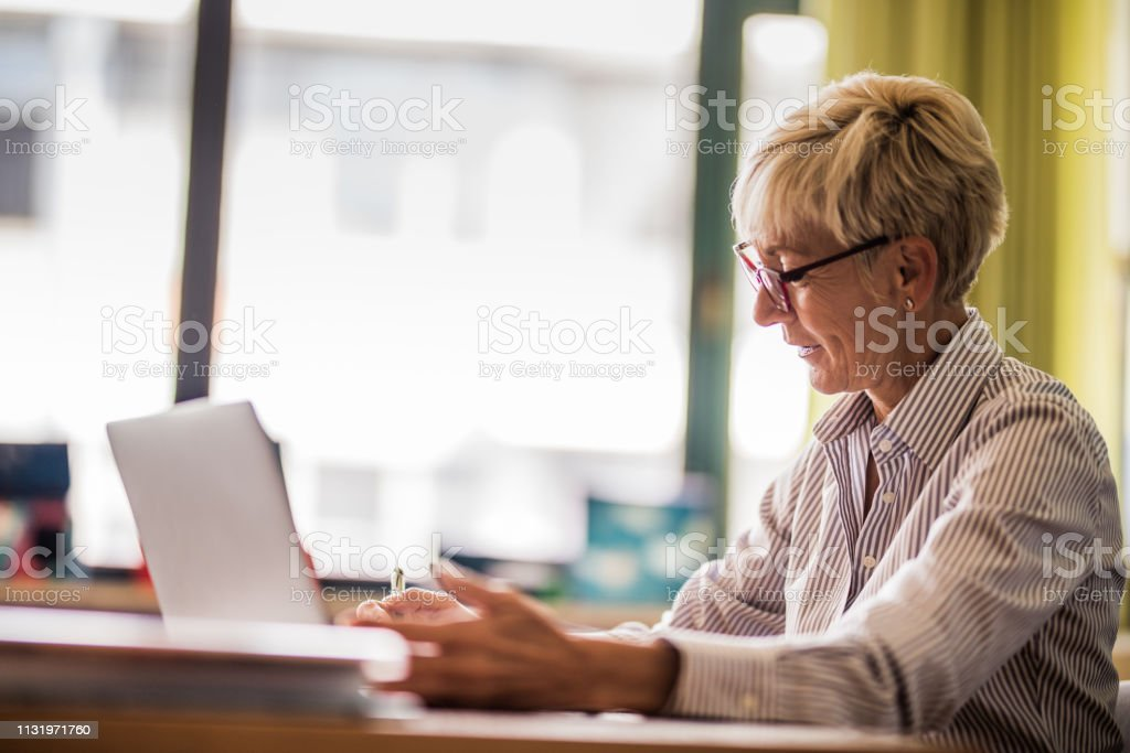 Smiling senior teacher taking notes in the classroom. Happy mature female teacher writing notes in her notebook in the classroom. Active Seniors Stock Photo