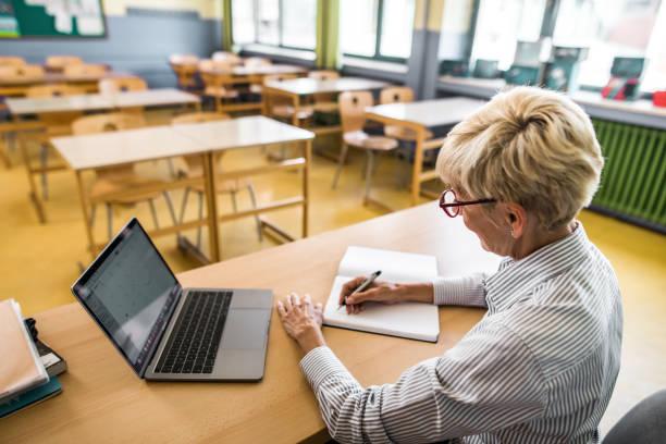 smiling senior teacher taking notes in the classroom. - professore di scuola superiore foto e immagini stock