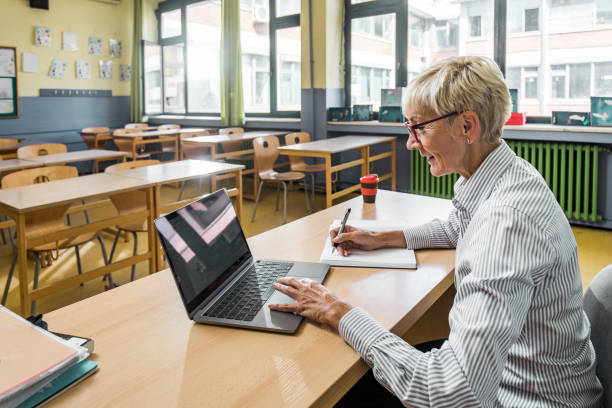 Smiling senior teacher taking notes while using laptop in the classroom. stock photo