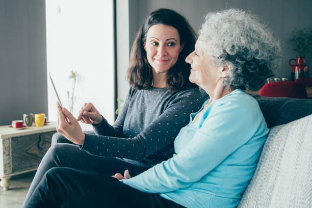 smiling senior woman and her daughter using tablet computer - filhos adultos imagens e fotografias de stock