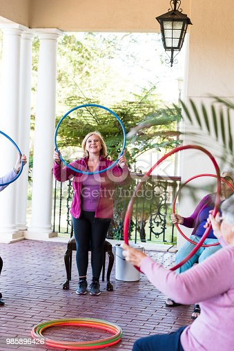 1047537292istockphoto Smiling senior woman at a fitness class holding a plastic hoop at shoulder height 985896426