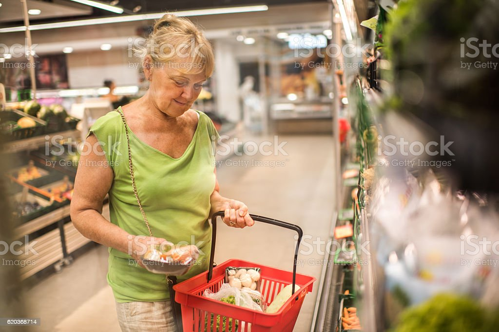 Smiling senior woman buying groceries in a supermarket. zbiór zdjęć royalty-free