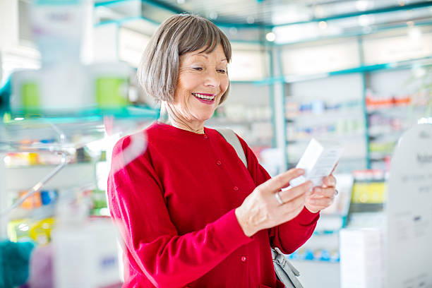 lächelnd ältere frau den kauf von medikamenten - lieblingsrezepte stock-fotos und bilder
