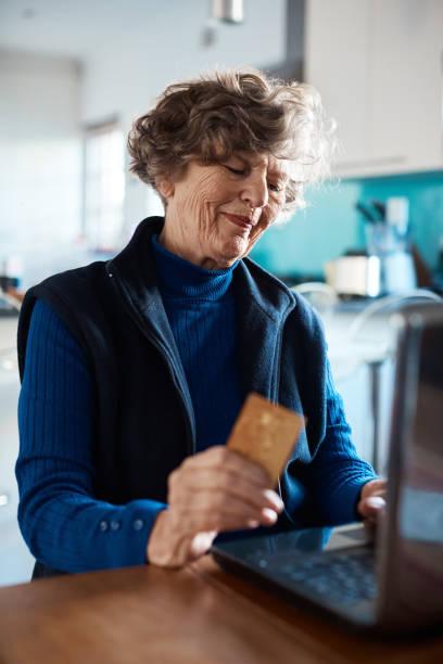 Lächelnde Seniorin beim Online-Shopping – Foto