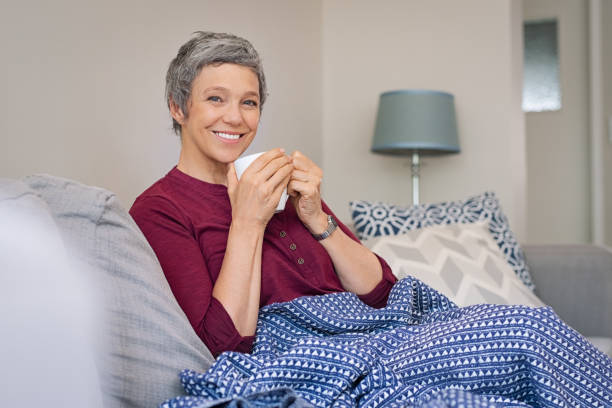 Smiling senior woman drinking coffee Portrait of smiling senior woman drinking coffee at home while looking at camera. Mature woman sitting on couch with warm blanket wrapped around leg. Happy lady relaxing at home with hot drink. wrapped in a blanket stock pictures, royalty-free photos & images