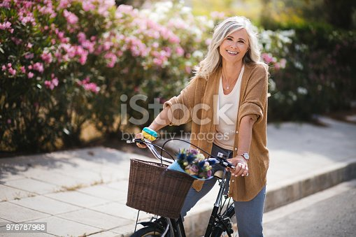 Happy active mature woman in fashionable clothes riding bicycle on suburban neighborhood street in spring