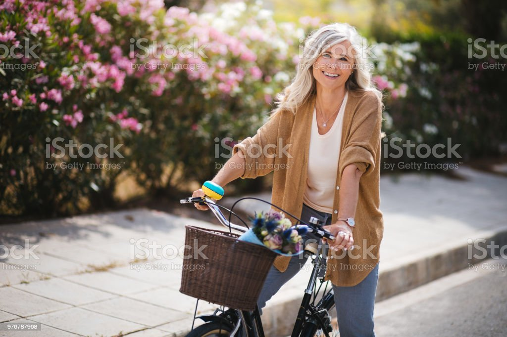 Smiling senior woman having fun riding vintage bike in spring stock photo