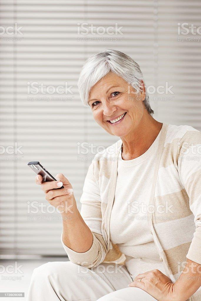 Smiling senior woman holding cellphone stock photo