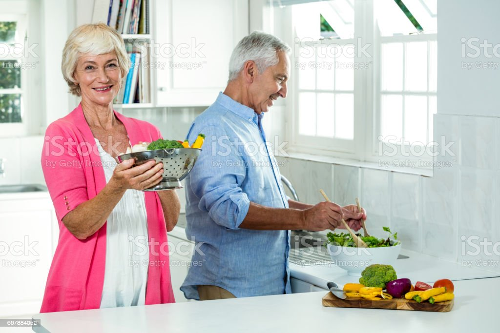 Smiling senior woman holding colander with man preparing vegetables royalty-free stock photo