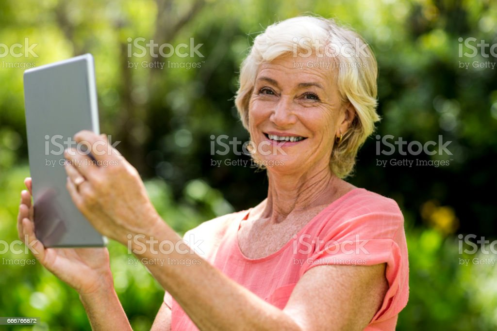 Smiling senior woman holding tablet in yard foto stock royalty-free