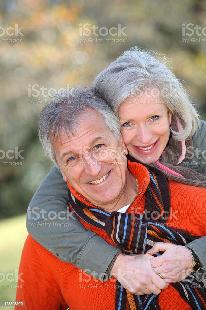A smiling senior woman hugs her husband from behind  royalty-free stock photo
