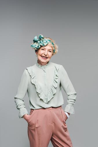 세련 된 옷을 입고 회색에 고립 된 카메라 보고 웃는 고위 여자 노인에 대한 스톡 사진 및 기타 이미지