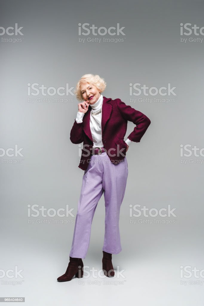smiling senior woman in stylish clothes looking at camera on grey royalty-free stock photo
