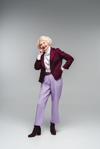 세련 된 옷을 입고 회색에 카메라 보고 웃는 고위 여자 노인에 대한 스톡 사진 및 기타 이미지
