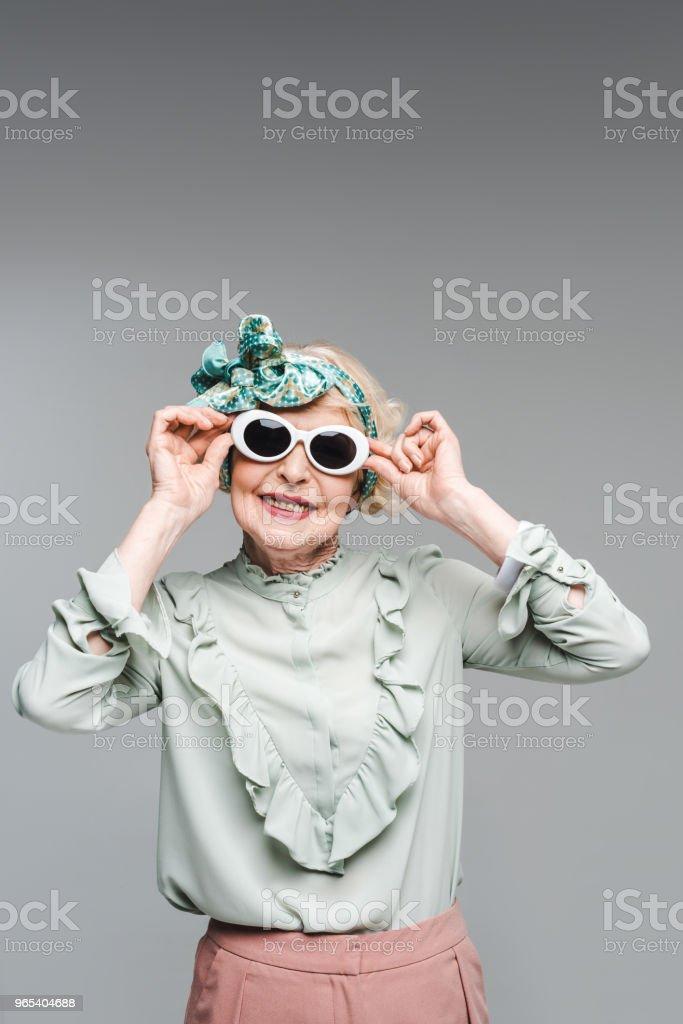femme senior souriante serre-tête élégant et lunettes de soleil isolés sur fond gris - Photo de A la mode libre de droits
