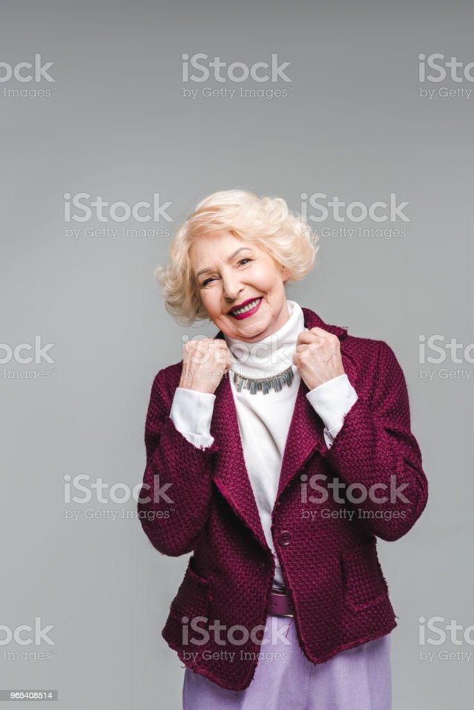smiling senior woman in stylish jacket and turtleneck isolated on grey royalty-free stock photo