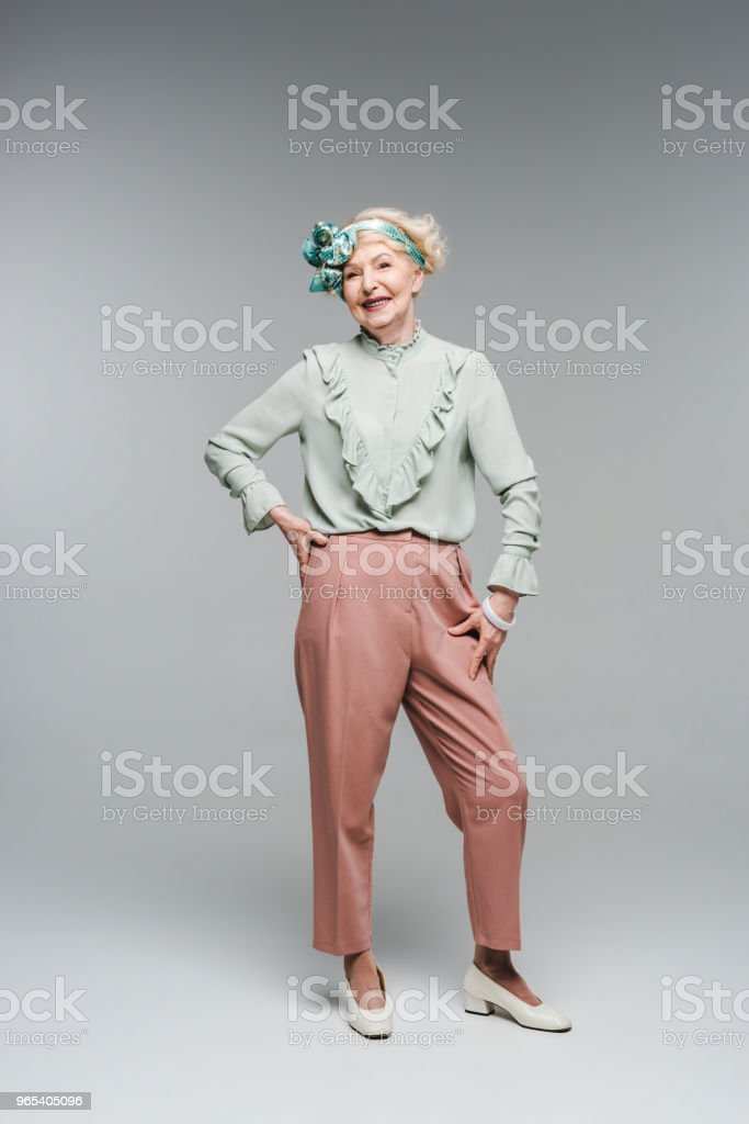 smiling senior woman in stylish vintage clothes on grey zbiór zdjęć royalty-free