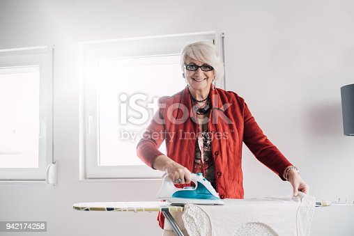 524159504 istock photo Smiling senior woman ironing the laundry 942174258