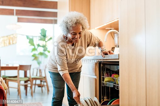 Smiling senior woman keeping plates in dishwasher. Retired elderly female is doing routine chores in kitchen. She is in casuals at home.