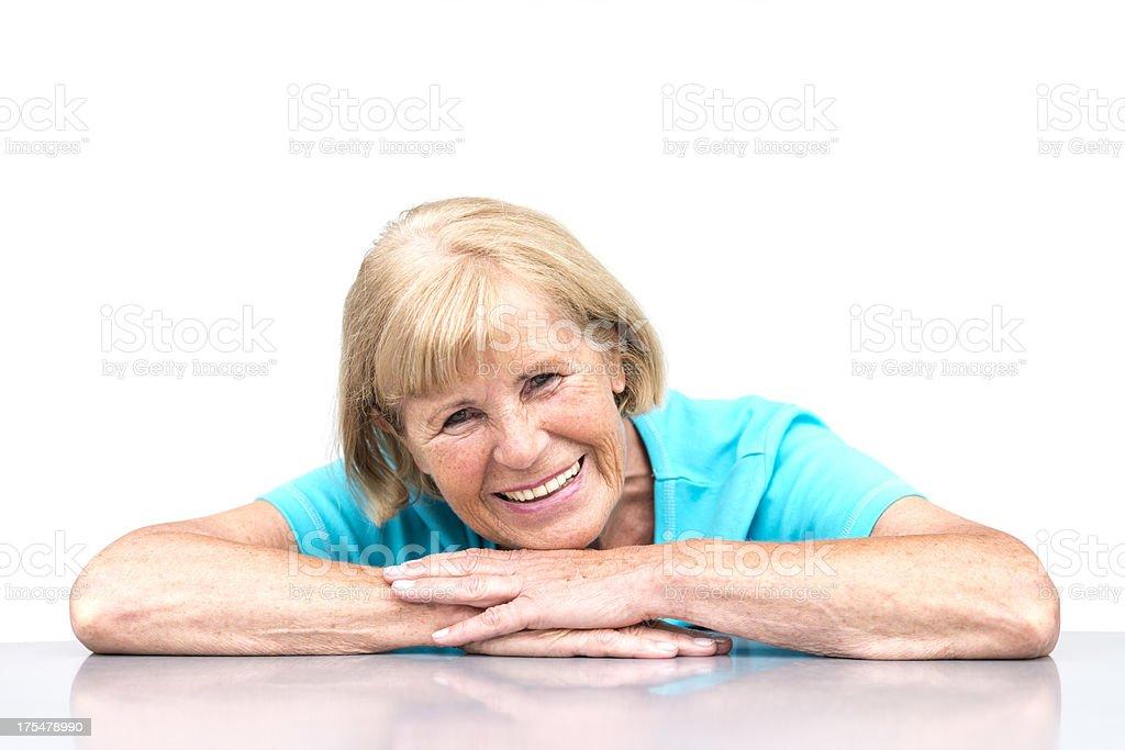 smiling senior woman leaning on desk royalty-free stock photo
