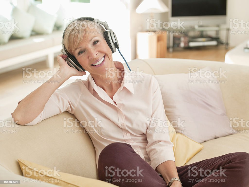 Smiling senior woman listening music while sitting on couch, portrait royalty-free stock photo