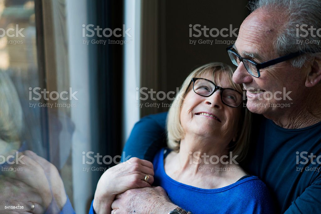 Smiling senior woman looking at man by window stock photo