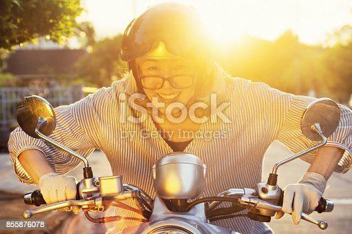 istock Smiling senior woman over 50 rides motorcycle at sunset 855876078