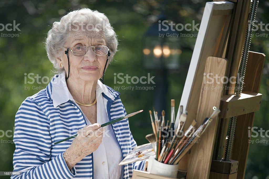 Smiling Senior Woman Painting royalty-free stock photo