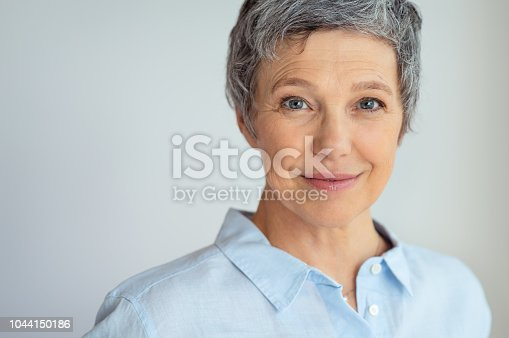 Closeup face of senior business woman standing against grey background with copy space. Portrait of successful woman in blue shirt feeling confident and looking at camera. Happy mature woman face standing.