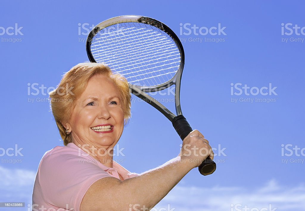 A smiling senior woman playing tennis against a blue sky royalty-free stock photo