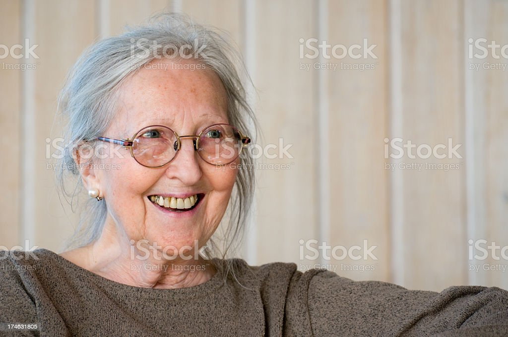 Smiling senior woman portrait wearing gray jumper stock photo