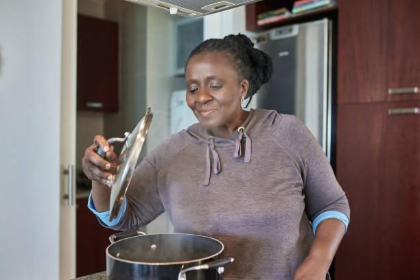 Smiling senior woman preparing meal in saucepan stock photo