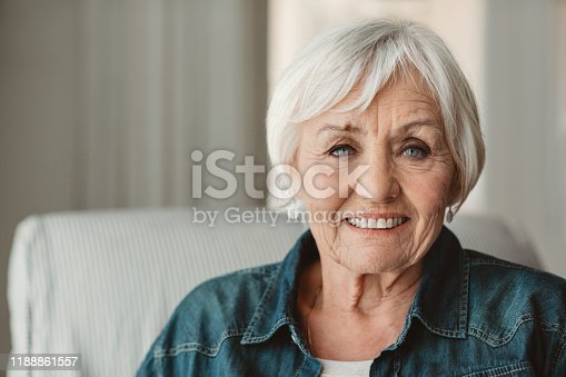 Portrait of a smiling senior woman sitting on a chair in her living room at home