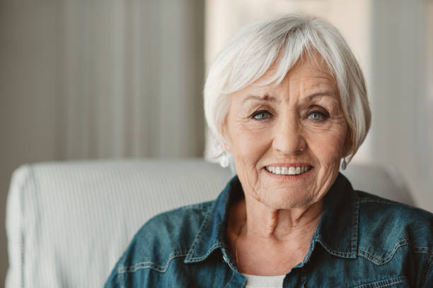 Smiling senior woman relaxing at home in the afternoon stock photo