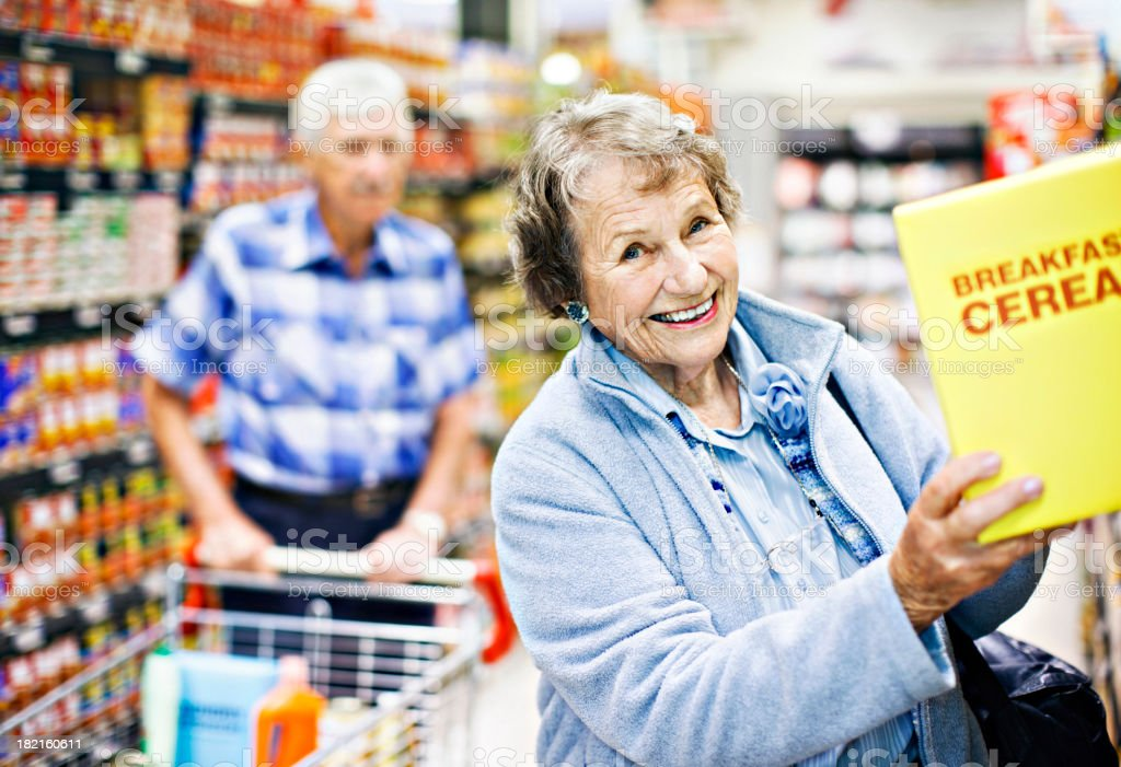 Smiling senior woman selects cereal as husband looks on stock photo