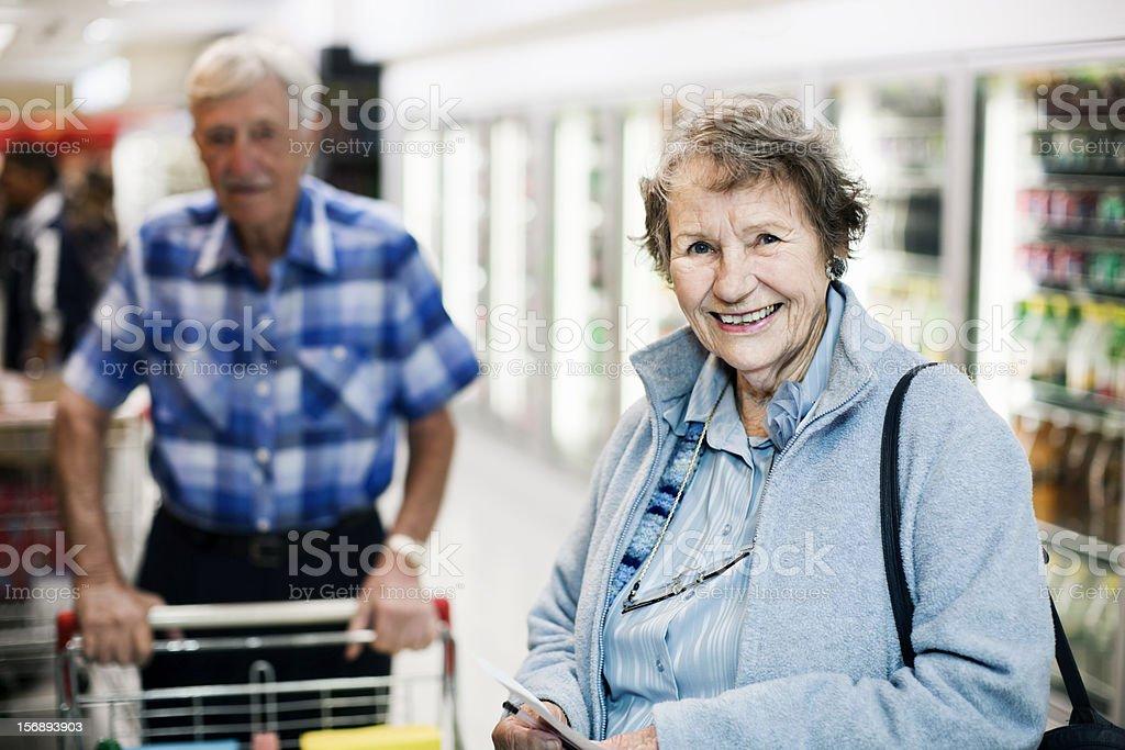 Smiling senior woman shopper in supermarket aisle, husband behind her stock photo