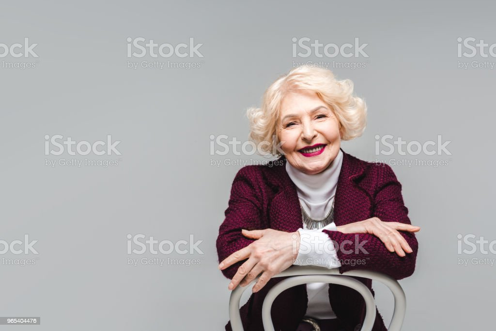 smiling senior woman sitting on chair and looking at camera isolated on grey zbiór zdjęć royalty-free